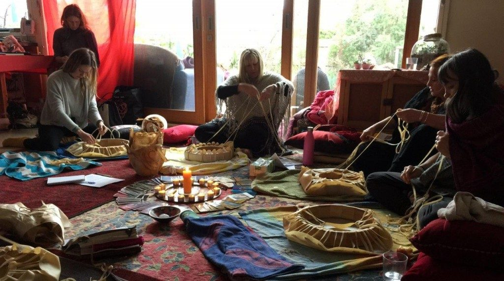 four women lacing the hides of shamanic drums