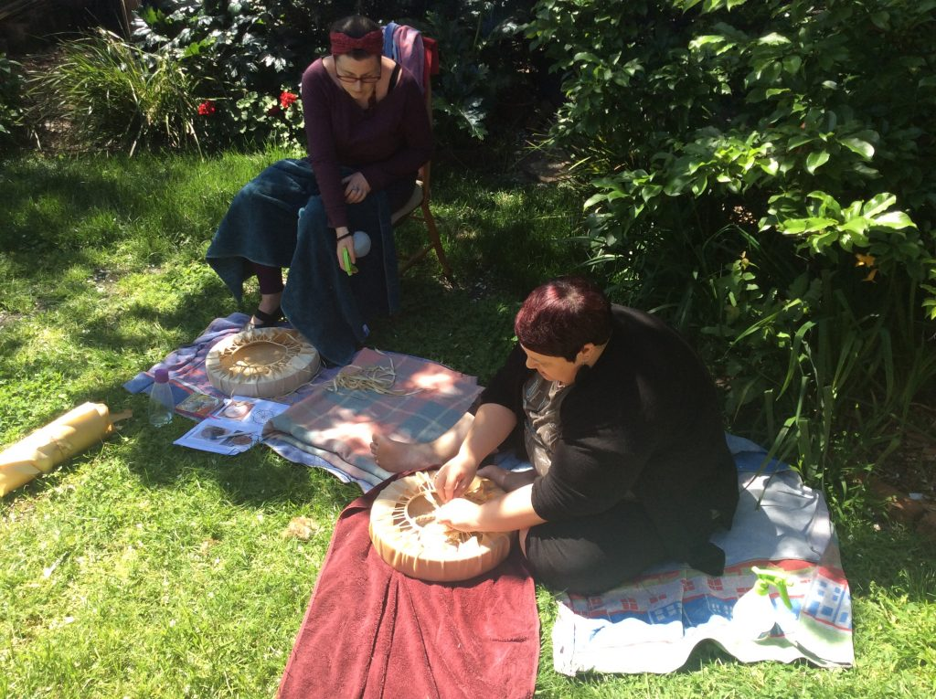 two women finishing making their drums in the garden.